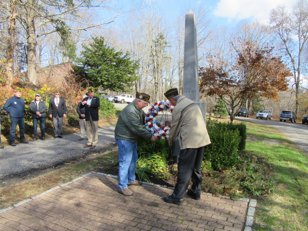 Bob Brown and Gene Roberts place the wreath in front of the VFW Monument.